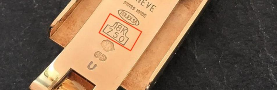 750 và 18k được khắc chung với nhau trên đồng hồ vàng